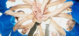 Gruppe med fotballspillere samlet i sirkel med hendene i midten